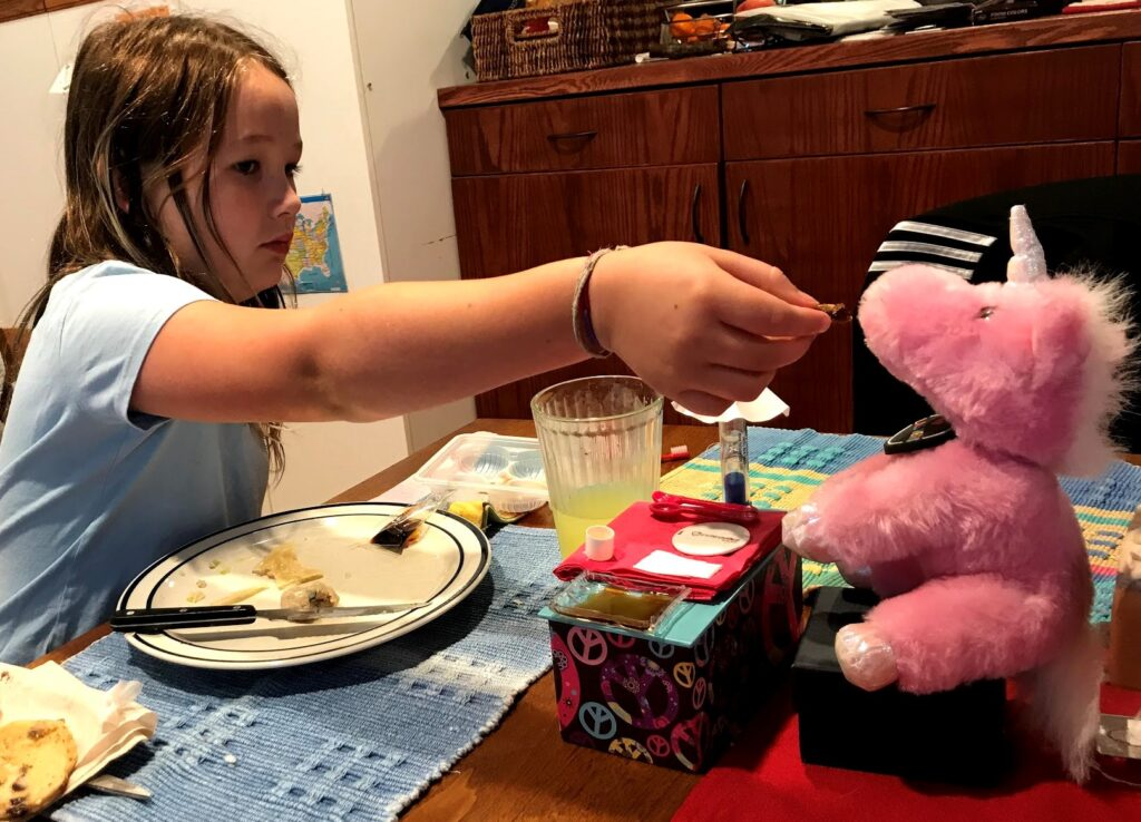 Etta feeding breakfast to her unicorn stuffy